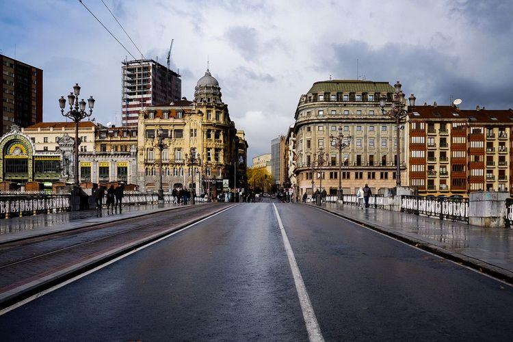 Road amidst buildings in city against sky