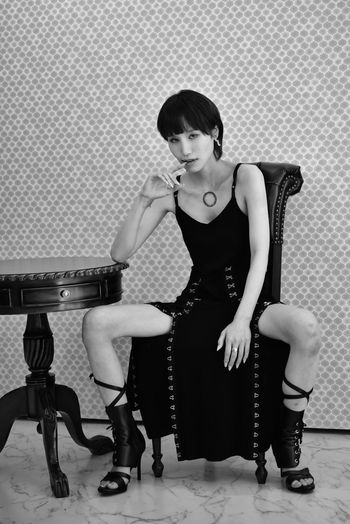 Full length of young woman sitting on chair