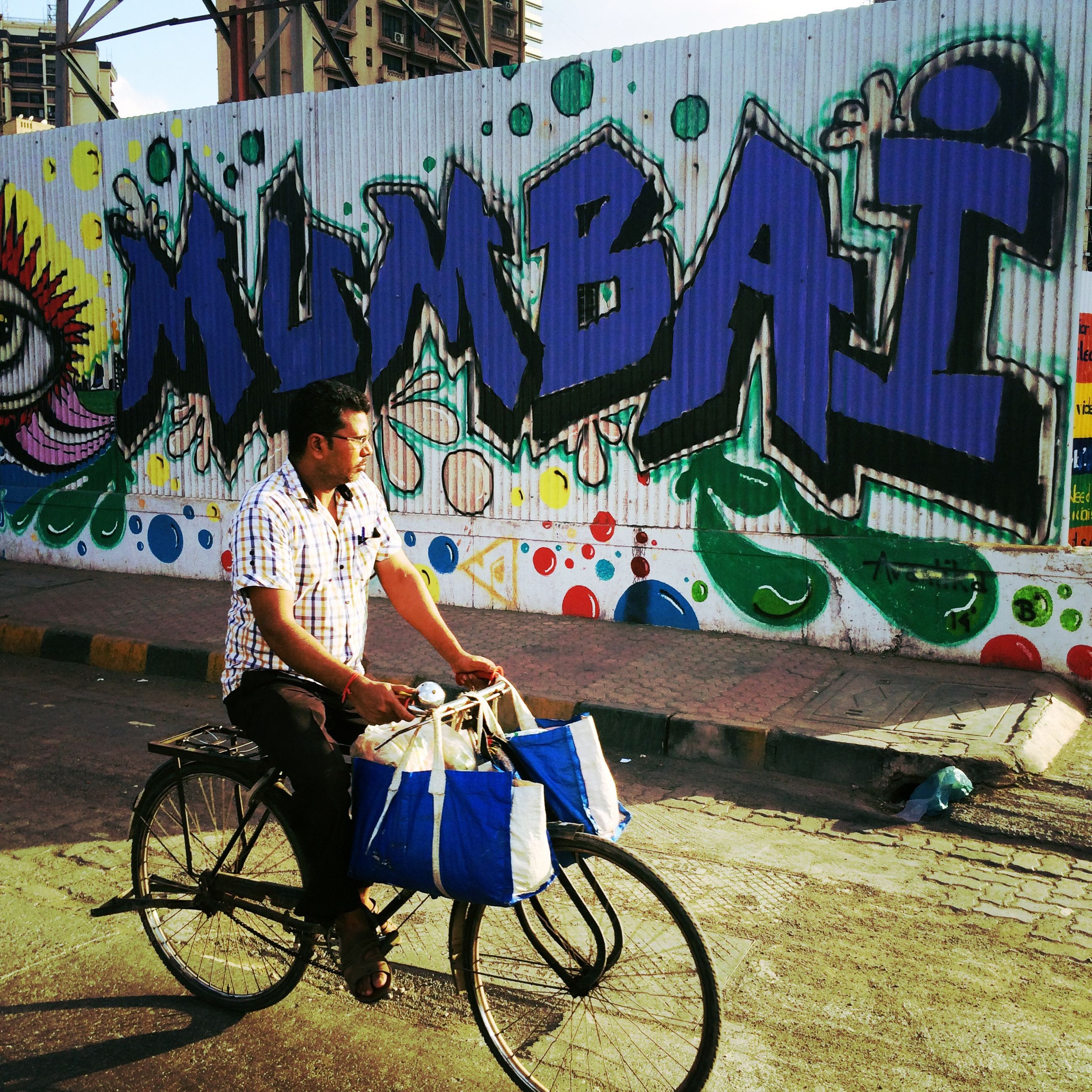 bicycle, graffiti, parking, stationary, transportation, land vehicle, parked, mode of transport, wall - building feature, built structure, text, absence, architecture, day, building exterior, western script, sunlight, outdoors, multi colored, no people