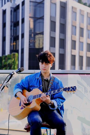Young man playing guitar against building