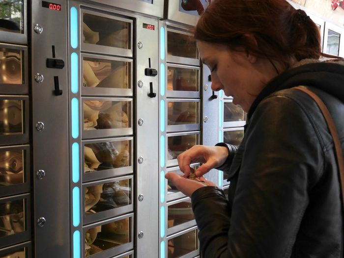 Woman counting coins by electric lockers