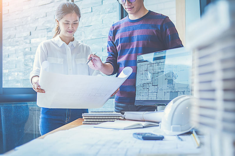Adult ARCHITECT Blueprint Business Business Person Communication Cooperation Coworker Design Professional Development Indoors  Males  Men Office Plan Planning Standing Teamwork Two People Women Working