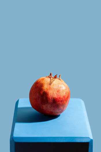 Close-up of apple on table against blue background