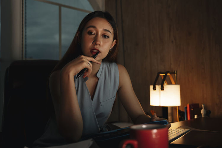 Portrait of young woman using phone while sitting on table