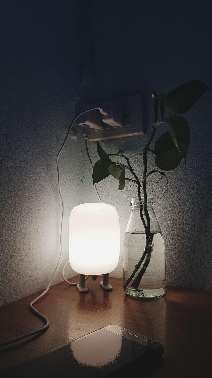 ILLUMINATED LAMP ON TABLE BY WALL