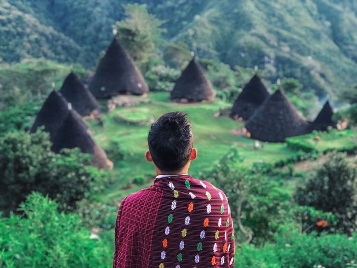 Rear view of man standing against huts on mountain