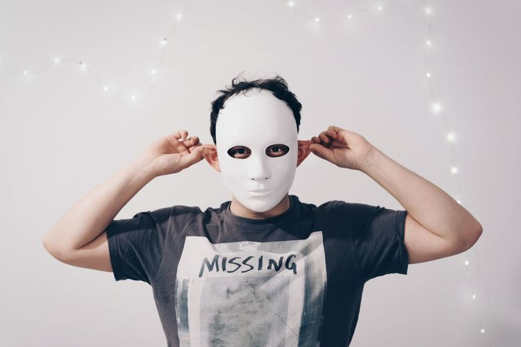 Portrait Of Man Wearing Mask While Holding Ears Against String Lights Decorated White Wall