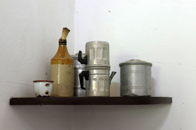 Close-up of wine bottles on table against wall