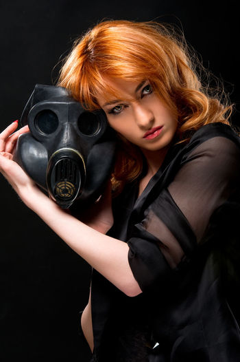 Portrait of young woman holding gas mask against black background