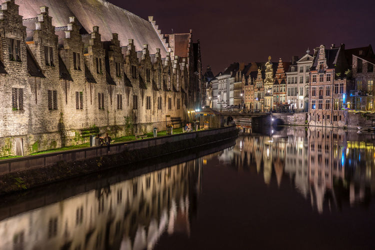 Buildings reflecting on canal in city at night