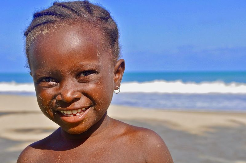 Portrait of happy girl at beach against sky