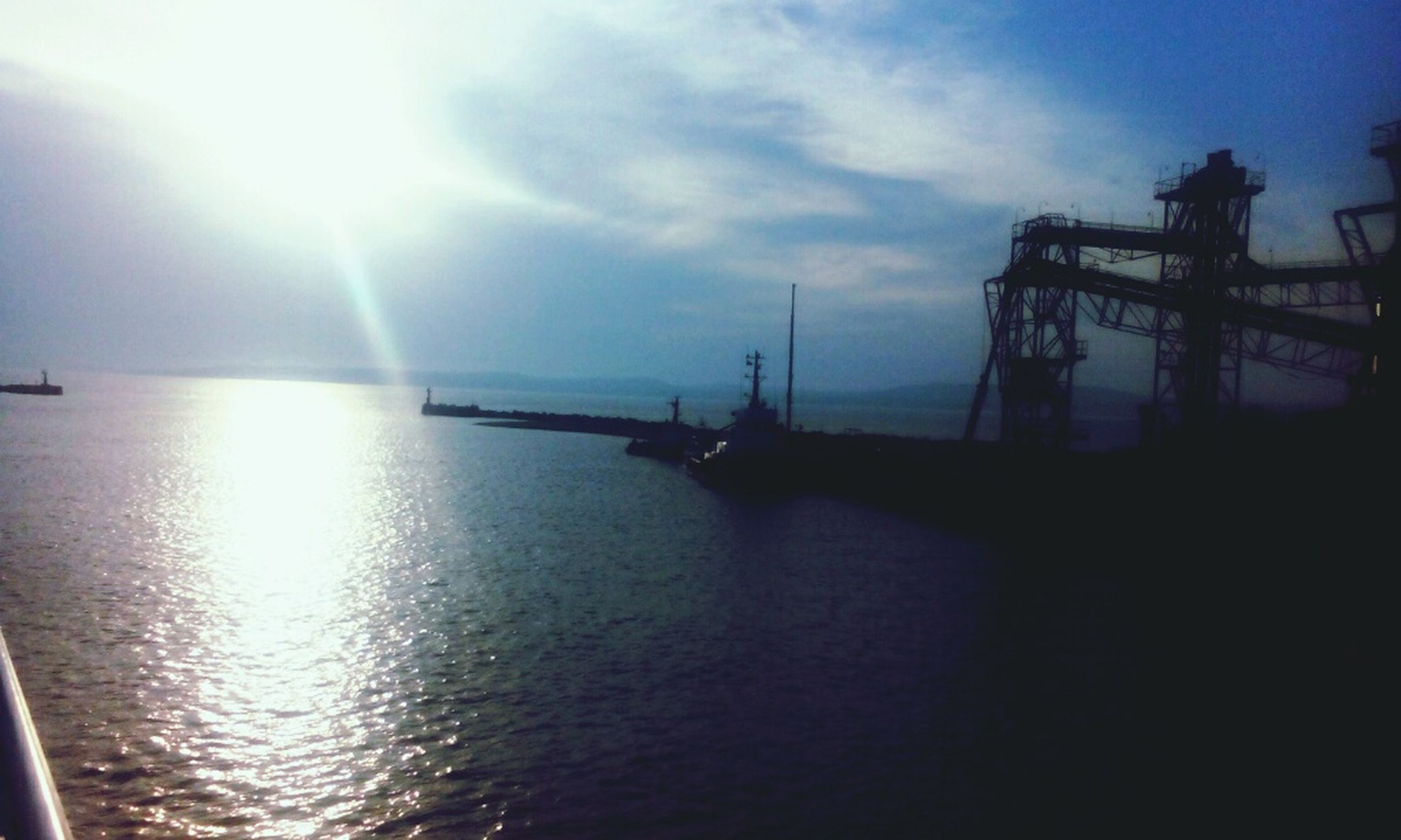 water, sea, nautical vessel, sky, transportation, waterfront, sun, silhouette, tranquility, mode of transport, sunset, tranquil scene, nature, boat, scenics, harbor, reflection, beauty in nature, sunlight, crane - construction machinery