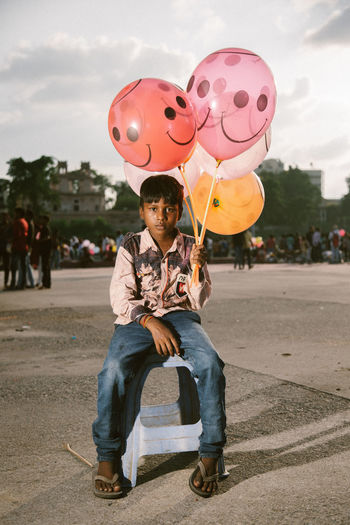 Full length of a boy holding balloons