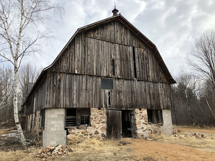 Old wooden rustic barn with stone foundation Abandoned Architecture Bare Tree Barn Barn, Rustic, Building Exterior Built Structure Day House Nature No People Outdoors Run-down Sky Tree Wood - Material