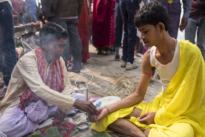 A young man has his fortune told during the Sonepur Mela festival, Bihar Bihar Day Fire Fortuneteller Hajipur Hands India Lifestyles Men Mystic Outdoors Real People Share Smoke Sonepur Sonepurmela Traditional Clothing Travel Travel Photography Travelphotography Yellow Color