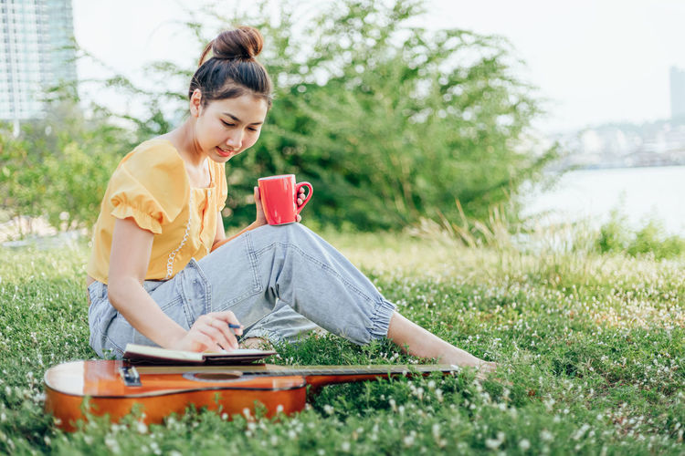 Full length of woman writing on book while having drink at park