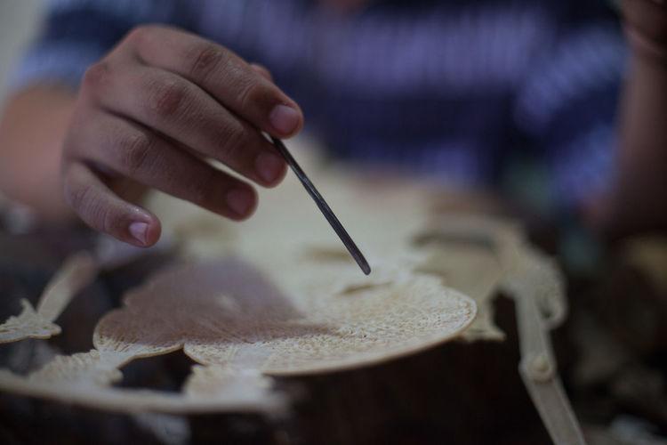 Midsection of man making handicraft in workshop