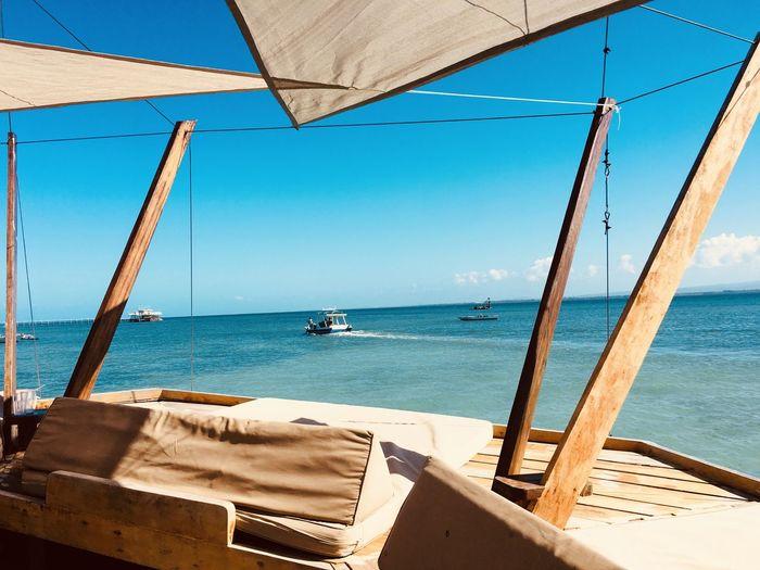 Sailboats on sea against clear sky