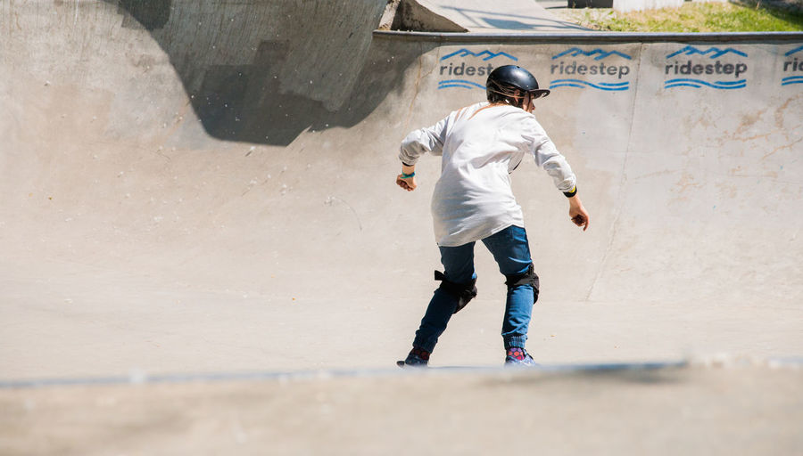 girl skateboarding in a skatepark Full Length One Person Casual Clothing Real People Lifestyles Leisure Activity Day Rear View Architecture Standing Men Sport Clothing Wall - Building Feature Outdoors Built Structure Nature Sunlight Walking Jeans