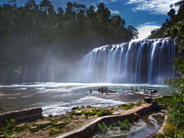 Scenic view of tinuy-an falls by trees against sky