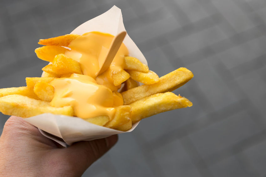 Man's hand holds a paper cone with french fries and creamy cheese as topping Belgium Eating Fries Ready To Eat Cheese Chips Close-up Creamy Culture Finger Food French Fries Fried Hand Holding Outdoors Portion Potato Prepared Potato Snack Take Out Food Temptation Topping Unhealthy Eating Urban