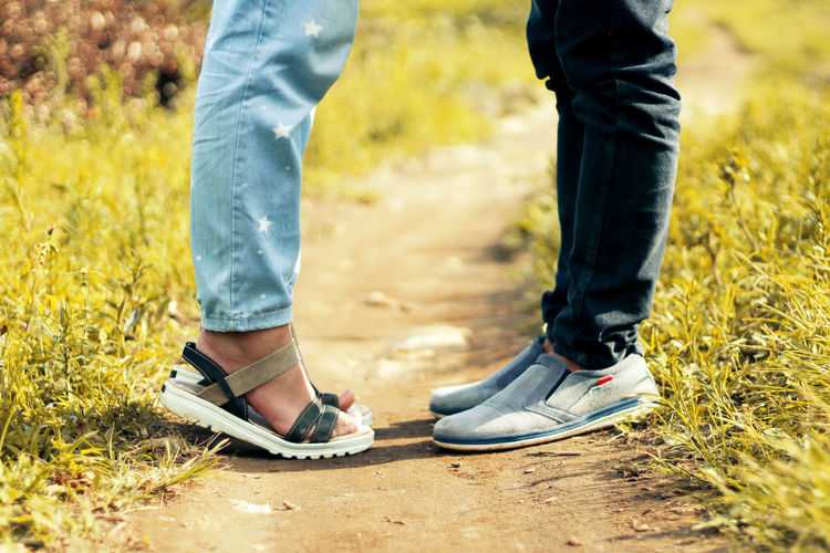 Low section of couple standing on footpath