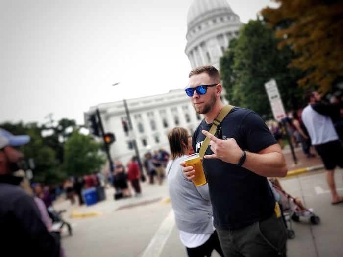 Man wearing sunglasses and holding beer standing outdoors
