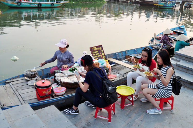 Tourists having meal at boat restaurant in Hoi An, Vietnam. Backpackers Boats Cafés Cooking Dining Eating Friends Hoi An Plastic Furniture Restaurants Rivers Tourism