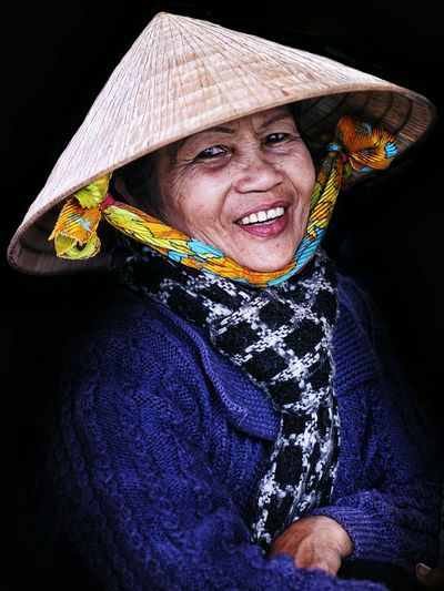Portrait of smiling senior woman wearing asian style conical hat against black background
