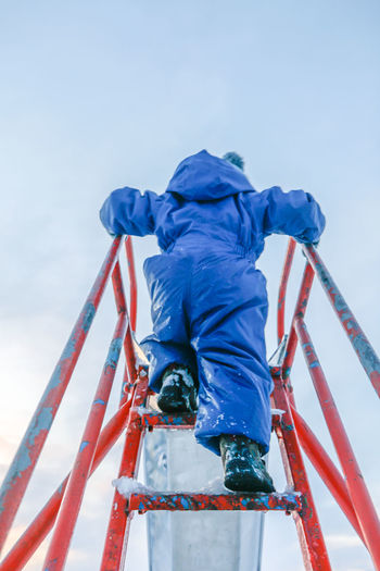 Child climbing up stairs to slide in play area, on a winter day Anticipation Ascending Brave Playground Equipment Blue Child Childhood Climbing Clothing Courage Day Full Length Leisure Activity Lifestyles One Person Outdoors Play Playground Playing Real People Rear View Sky Slide - Play Equipment Warm Clothing Winter