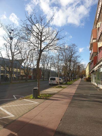 Street by buildings in city against sky