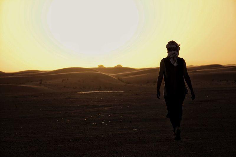Silhouette of man walking in desert during sunset