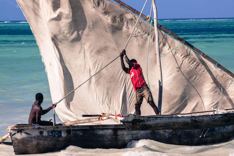 Fishermen sailing in boat on sea