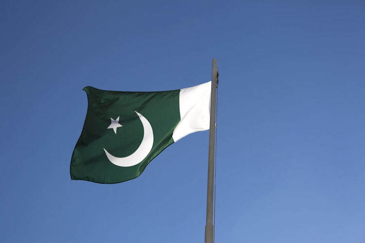 Low angle view of pakistan flag against clear blue sky