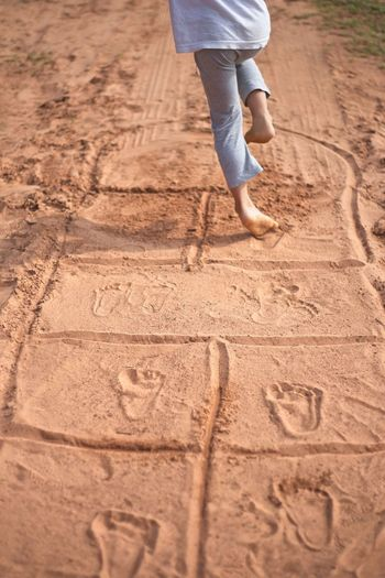 Low section of child playing hopscotch on sand