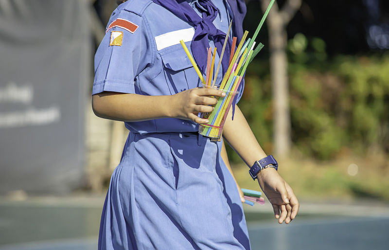 Midsection of schoolgirl holding disposable container with straw on footpath