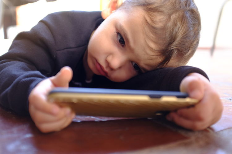 Close-up portrait of boy using mobile phone