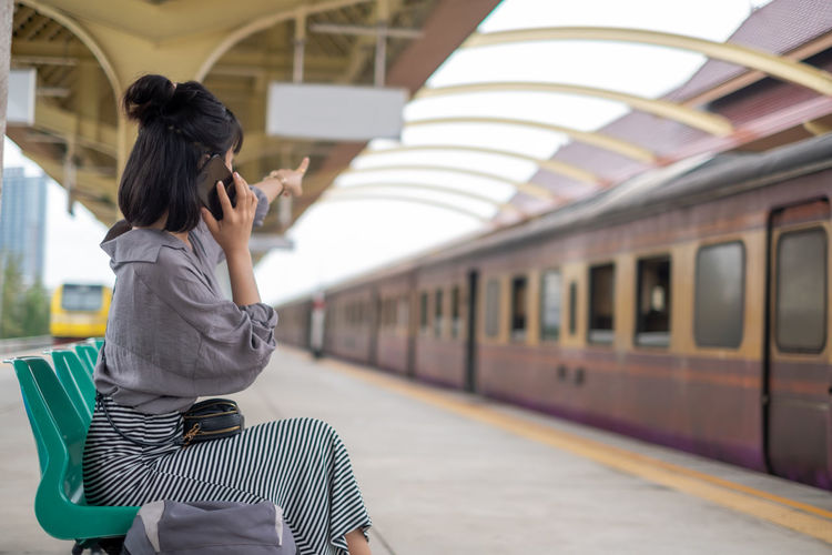 Full length of woman holding train at railroad station