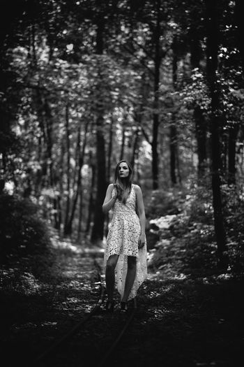 Portrait Of Young Woman Standing On Footpath In Forest