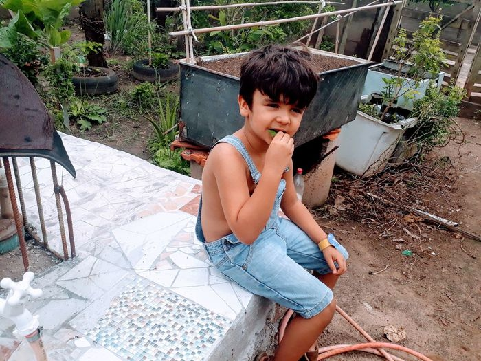 High angle view of boy eating while sitting by water pump in yard
