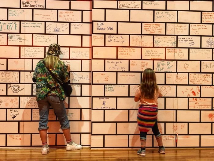 Rear view of women standing against brick wall