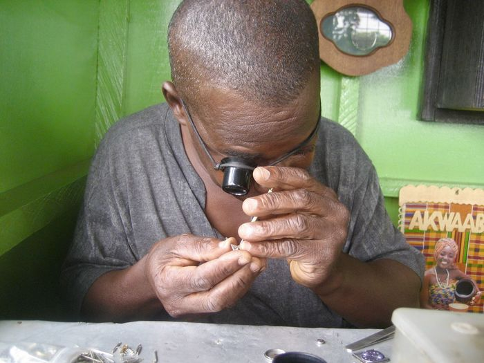 Concentration Africa Man Craft Repair Clockwork Adult Tweezers Magnifying Glass Concentrated Holding Front View Occupation Watchmaker Enlarge Craftman Craftmanship Handwork One Person Small Business Enlargement Men Indoors  Technology Males  Headshot Work Tool Portrait Sitting Equipment Skill  Table