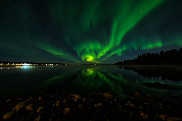 Aurora borealis over river against sky at night
