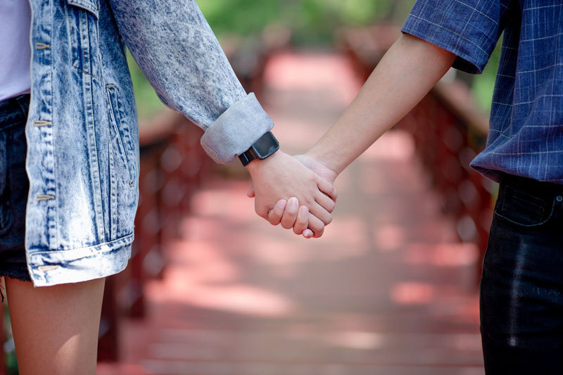 Midsection of couple holding hands on footbridge
