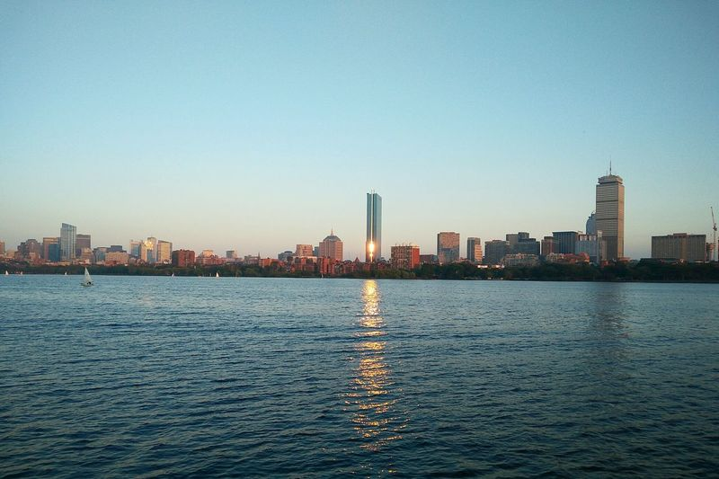 City skyline by river against clear sky