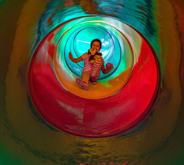 Full length portrait of girl in tunnel slide