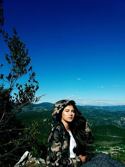 Portrait Of Young Woman Wearing Camouflage Clothing Against Blue Sky