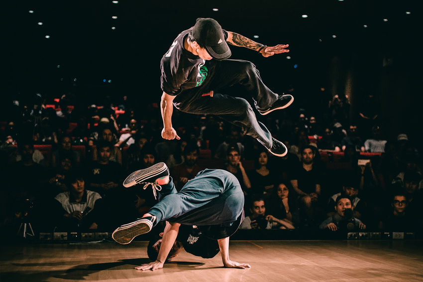 BBOY Adult Arts Culture And Entertainment Balance Breakdancing Crowd Dancing Full Length Group Of People Hip Hop Indoors  Jumping Large Group Of People Leisure Activity Lifestyles Men Motion Performance Performing Arts Event Real People Skill  Skills  Spectator Stage Stage - Performance Space Watching