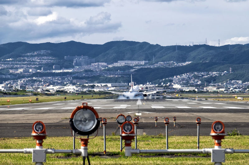 Airplane on airport runway against mountains