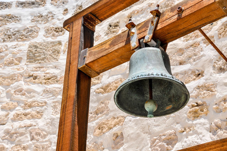 Old patina curfew bell on wooden frame in outdoor limestone courtyard at the historic Round House in Fremantle, Western Australia. Architecture B Bell Brass Closeup Curfew Curfew Bell Device Fremantle, Western Australia Gaol Historic Limestone Metal Old Outdoors Patina Prison Replica  Ringing Signal The Round House Tourist Attrat Tradition Wall Wooden Frame